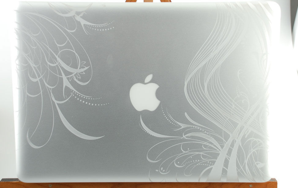 Macbook Pro engraved with swirly graphical pattern around the apple logo