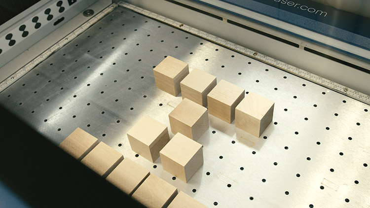 Wooden baby blocks layed out inside the laser engraver
