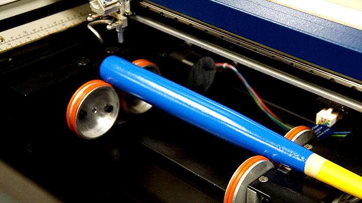 A mini baseball bat placed on a rotary device in the laser system