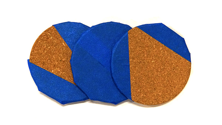 Cork coasters masked with tape for paint.