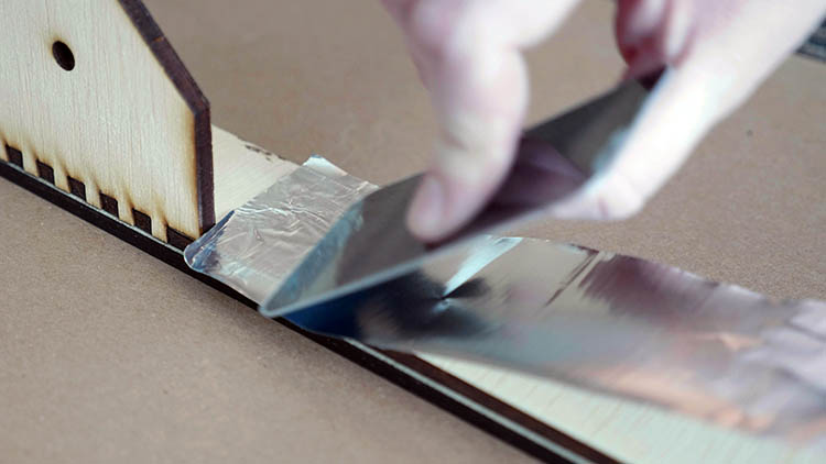 Applying foil tap to the inside of the laser-cut box sides.