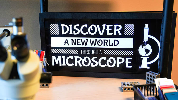 Finished LED-lit sign on a desk behind a microscope.